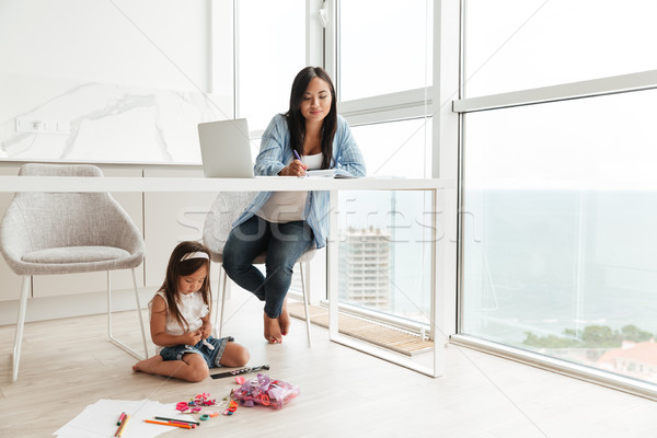 Concentrated woman write notes while her daughter sitting on floor. Stock photo © deandrobot