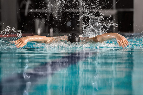 Male swimmer swimming the butterfly stroke Stock photo © deandrobot
