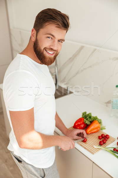 Vertical image of smiling bearded man cuts vegetables on kitchen Stock photo © deandrobot