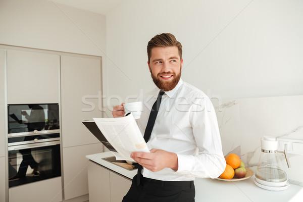 Glimlachend bebaarde zakenman drinken koffie lezing Stockfoto © deandrobot