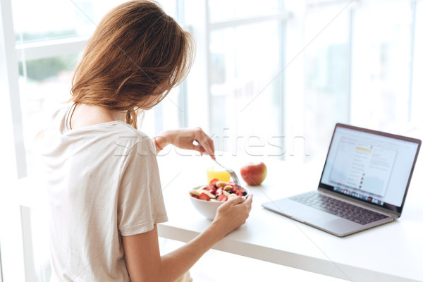 Back view of woman have breakfast and using laptop Stock photo © deandrobot