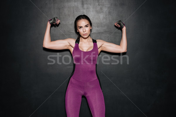 Confident woman in sportswear showing biceps and looking at camera Stock photo © deandrobot