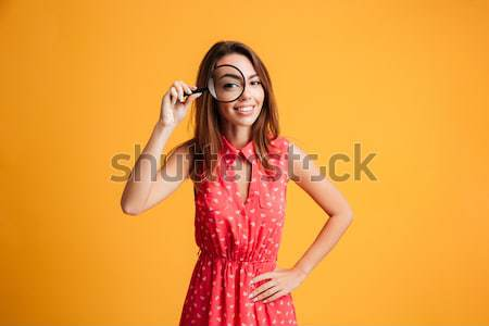 Pretty playful girl in dress showing peace gesture and winking Stock photo © deandrobot