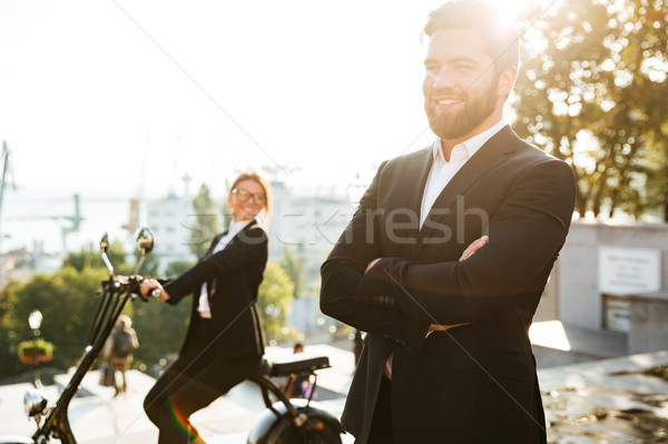 Smiling business man posing outdoors holding crossed arms Stock photo © deandrobot