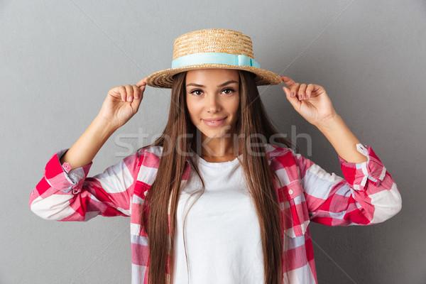 очаровательный прикасаться соломенной шляпе глядя камеры Сток-фото © deandrobot