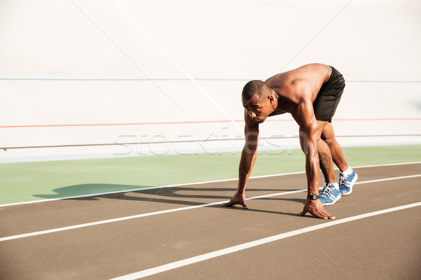 Young musculary african sports man in starting position ready to Stock photo © deandrobot