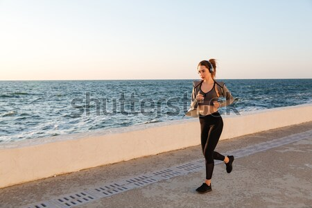 Beautiful sportive woman in headphones running at the seaside Stock photo © deandrobot
