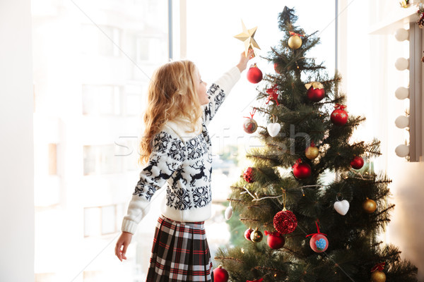 Cute little girl in knitted sweater placing star on the top of C Stock photo © deandrobot