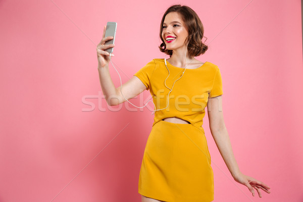 Portrait of a smiling woman in dress and make up Stock photo © deandrobot