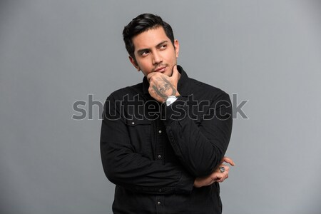 Concentrated thinking young handsome man Stock photo © deandrobot