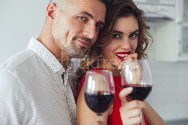 Portrait of lovers drinking wine and looking camera at home Stock photo © deandrobot