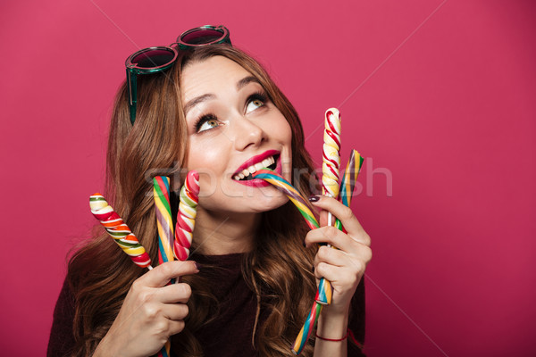 Young woman wearing glasses eating sweeties Stock photo © deandrobot