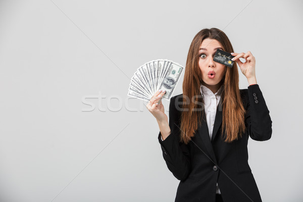 Funny lady grimacing and holding cash and credit card in hands Stock photo © deandrobot