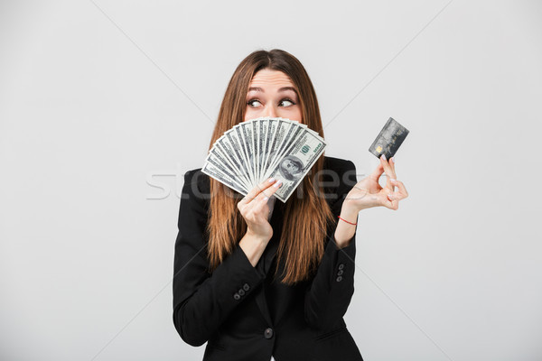Pretty lady hiding behind money and holding credit card isolated Stock photo © deandrobot