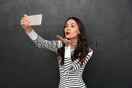 Confundirse morena mujer suéter senalando papel Foto stock © deandrobot