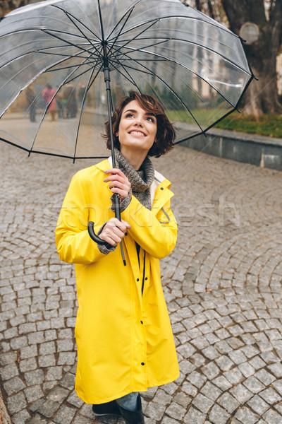 Zufrieden Erwachsenen Mädchen gelb Regenmantel stehen Stock foto © deandrobot