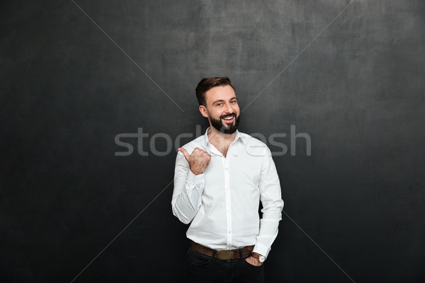 Joyous adult guy in office posing on camera, gesturing with thum Stock photo © deandrobot