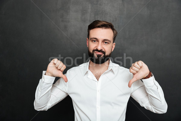 Picture of disappointed guy 30s gesturing on camera with thumbs  Stock photo © deandrobot