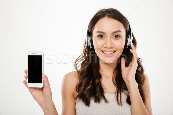 Tevreden brunette vrouw hoofdtelefoon tonen smartphone Stockfoto © deandrobot