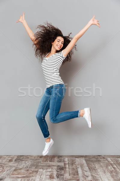 Joyous brunette female in casual posing on camera jumping with h Stock photo © deandrobot