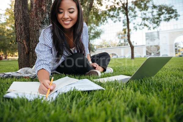 Close-up of pretty asian student with charming smile, keeping re Stock photo © deandrobot