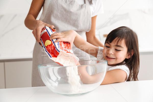 Foto dona de casa avental pequeno filha Foto stock © deandrobot