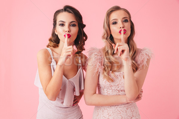 Two women in dresses having secret while showing silence gestures Stock photo © deandrobot