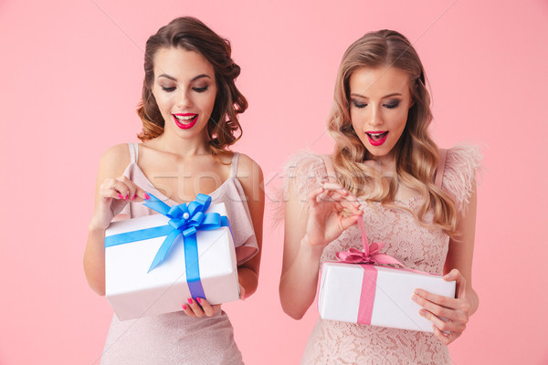 Two pleased women in dresses standing together and opening gift Stock photo © deandrobot