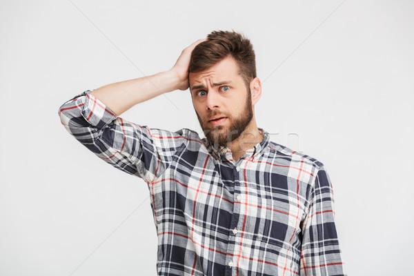 Portré zavart fiatalember kockás póló néz Stock fotó © deandrobot
