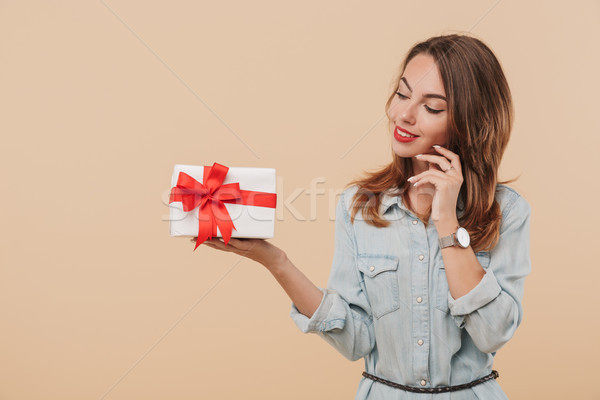 Portrait of a pensive young girl looking at present box Stock photo © deandrobot