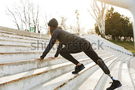 Image of disabled sportswoman with prosthetic leg in tracksuit,  Stock photo © deandrobot