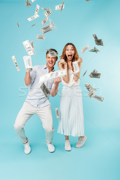 Emotional screaming caucasian loving couple over money. Stock photo © deandrobot