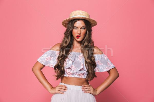 Portrait of serious pretty woman 20s wearing straw hat biting li Stock photo © deandrobot