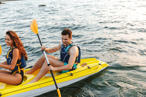 Loving couple kayaking on lake sea in boat Stock photo © deandrobot
