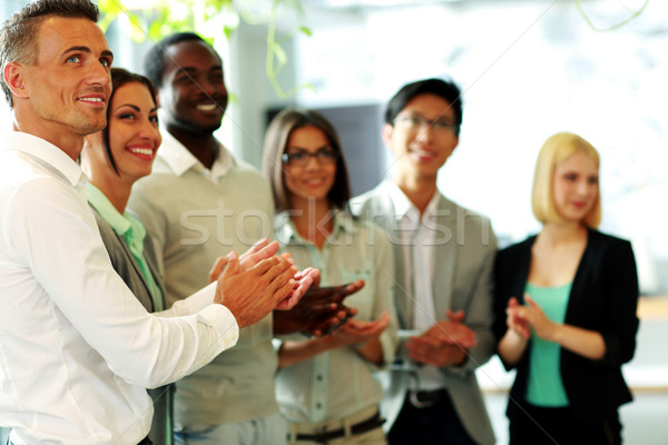 Group of a happy business team applauding Stock photo © deandrobot