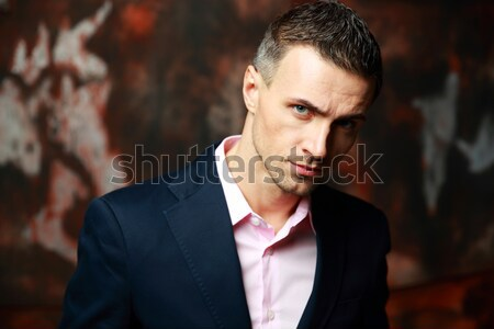 Trendy man standing and looking away over industrial background Stock photo © deandrobot