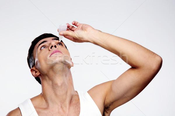 Handsome man applying eye drop over gray background Stock photo © deandrobot
