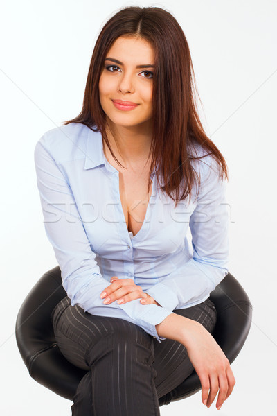 Portrait of a happy young business woman in blue shirt sitting o Stock photo © deandrobot