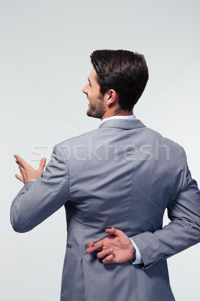 Businessman with fingers crossed Stock photo © deandrobot