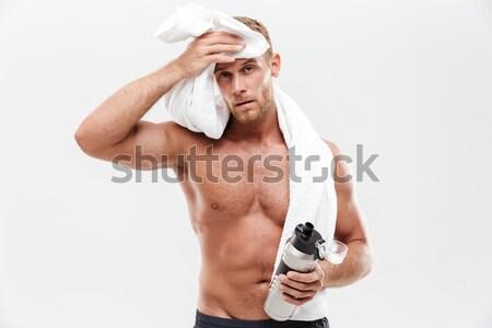 Young man applying hair spray to his hair Stock photo © deandrobot