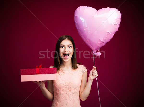Surprised woman holding heart shaped balloon and gift box Stock photo © deandrobot