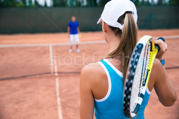 Woman playing in tennis with man outdoors Stock photo © deandrobot