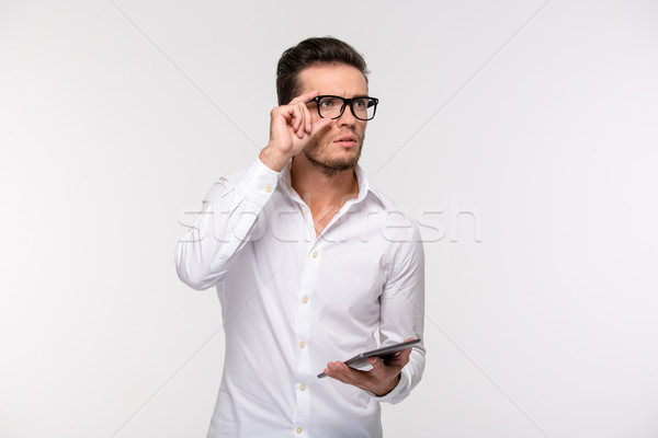 Pensive businessman holding tablet computer  Stock photo © deandrobot