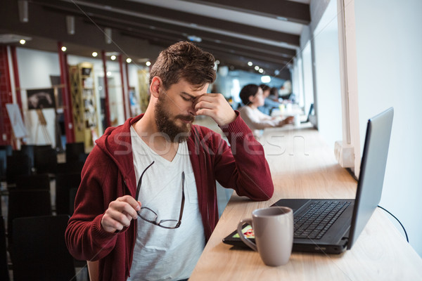 Young handsome bearded man tired using laptop Stock photo © deandrobot