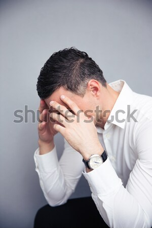 Depressed young man holding cellphone and rubbing eyes Stock photo © deandrobot