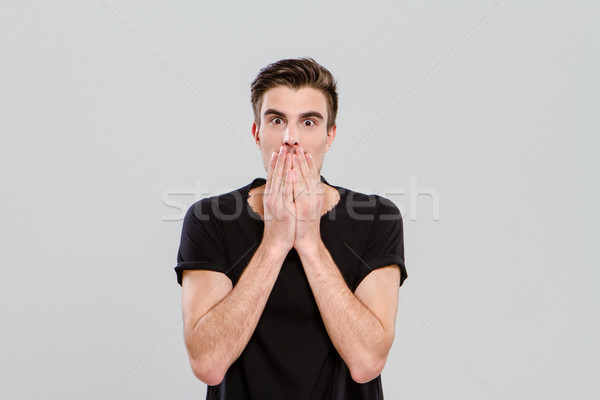 Young man surprised and closed mouth with hands Stock photo © deandrobot