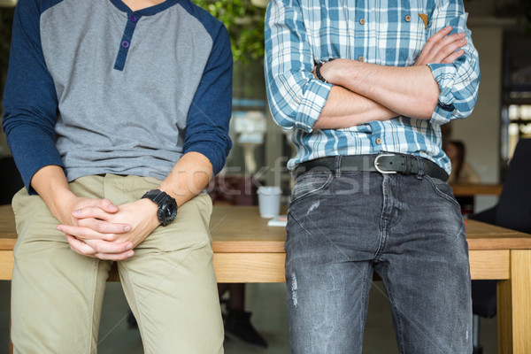 Two men standing with folded hands  Stock photo © deandrobot