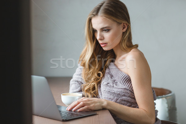 Thoughtful attractive girl drinking coffee and using laptop Stock photo © deandrobot