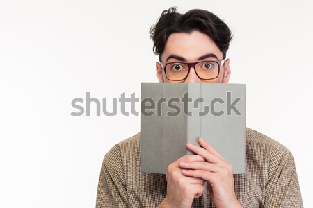 Young man covering his face with book Stock photo © deandrobot
