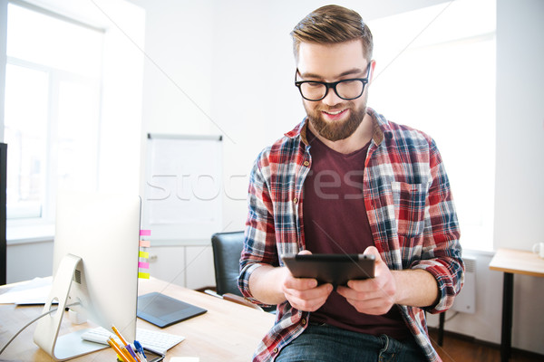 Happy handsome man with beard sitting and using tablet Stock photo © deandrobot